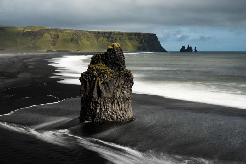 Basalt sea stack on a black sand beach