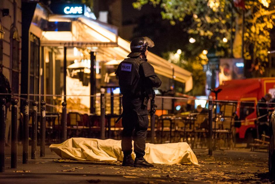 """Plusieurs attaques ont eclaté à de nombreux endroits de la capitale ce vendredi 13 novembre, au soir, faisant au moins 120 morts selon le procureur de la Republique de Paris. Un policier lourdement armé monte la garde non loin d'un corps recouvert d'un drap, au niveau de la station de métro """"filles du calvaire"""". © Julien MUGUET / hanslucas"""
