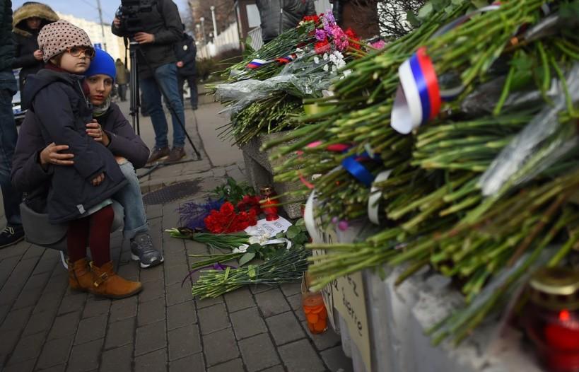 Des personnes déposant des fleurs devant l'ambassade de France à Moscou - © AFP / Dmitry Serebryakov