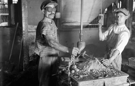 Automobiles Renault. D'une main l'ouvrier fait tomber le sable. Billancourt (Hauts-de-Seine) 1931-1934 Crédits: François Kollar