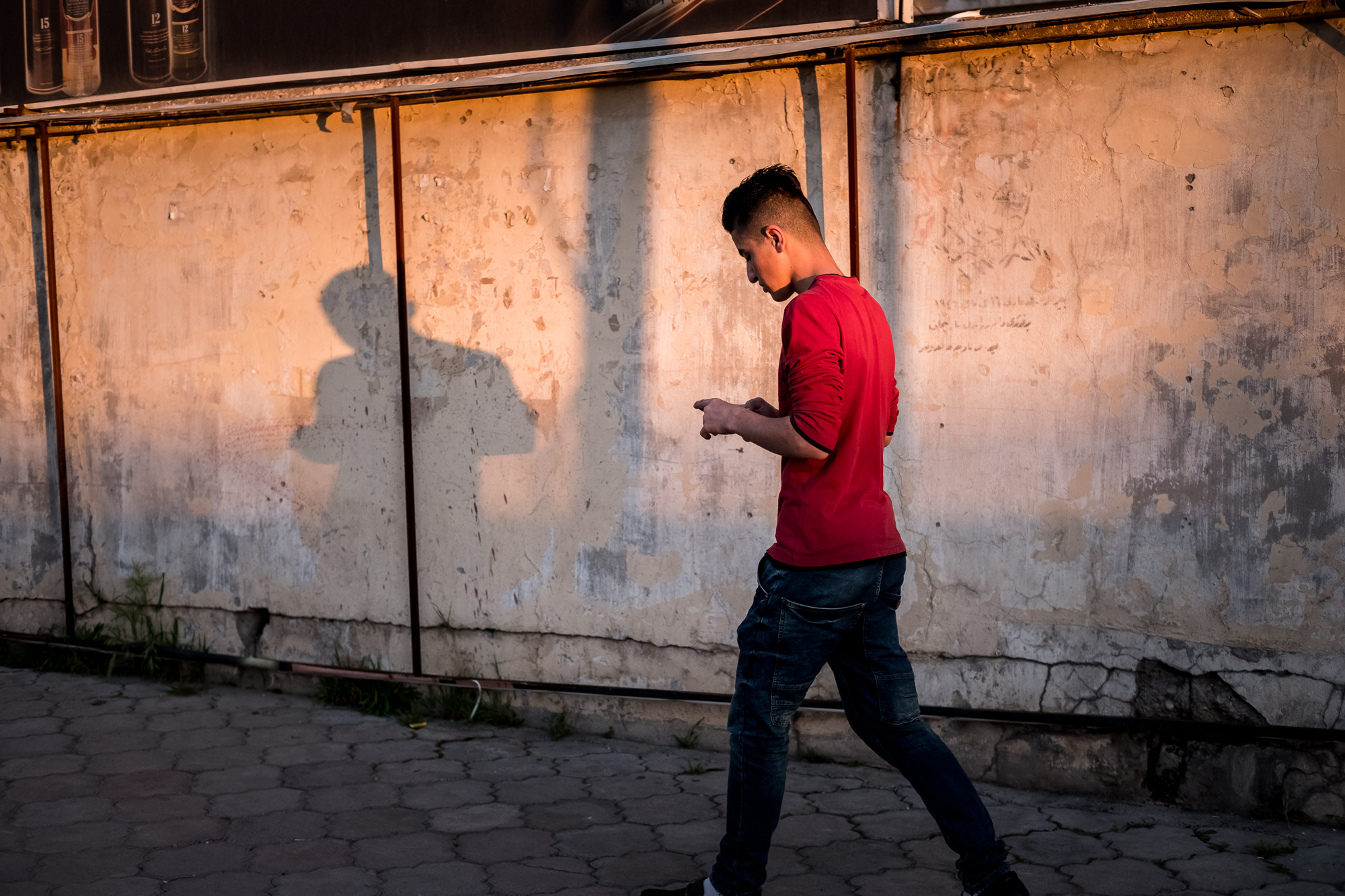 16 avril 2016 : Un homme marche dans une rue du quartier chrétien d'Ankawa, Erbil, Kurdistan irakien. Irak - © Jean-Matthieu Gautier / CIRIC - X-Pro 2 - XF 35mm f/2 WR à f/3.2 - 1/1250 - ISO 800