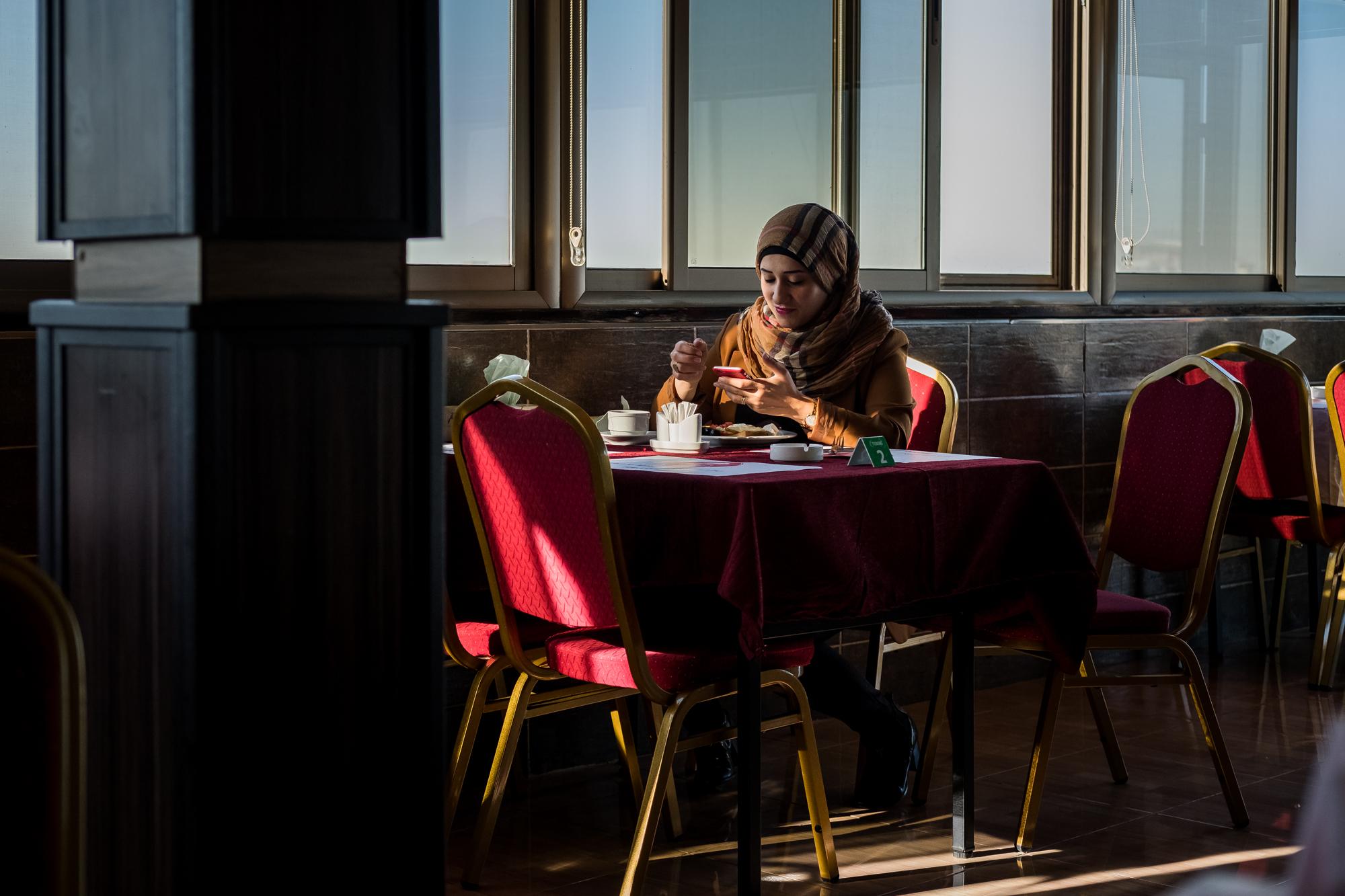 17 avril 2016 : une jeune femme kurde consulte son téléphone portable dans un restaurant du quartier chrétien d'Erbil, capitale du Kurdisan irakien, à moins de 80 kilomètres des lignes de Daech. Irak.- © Jean-Matthieu Gautier - X-Pro 2 - XF 35mm f/2 WR à f/2.8 - 1/680 - ISO 500