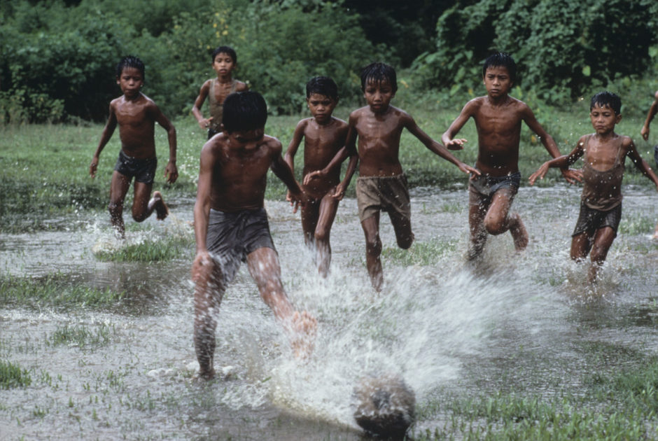 Boys playing soccer in the flooded pastures, Bangladesh, 1983