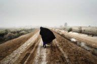 An Iraqi woman walks on a road south of Baghdad, Dec. 20, 2002.