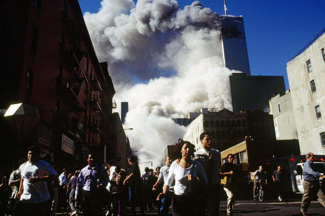 USA. New York City. September 11, 2001. Pedestrians on Church Street run from falling debris as Tower 2, the South Tower, of the World Trade Center collapses at 9:55 a.m. Tower 1, the North Tower, still standing here, collapsed at 10:29 a.m. Seven World Trade Center, the 47-story building seen immediately in front of Tower 1, collapsed at 5:25 p.m. – photo by Susan Meiselas