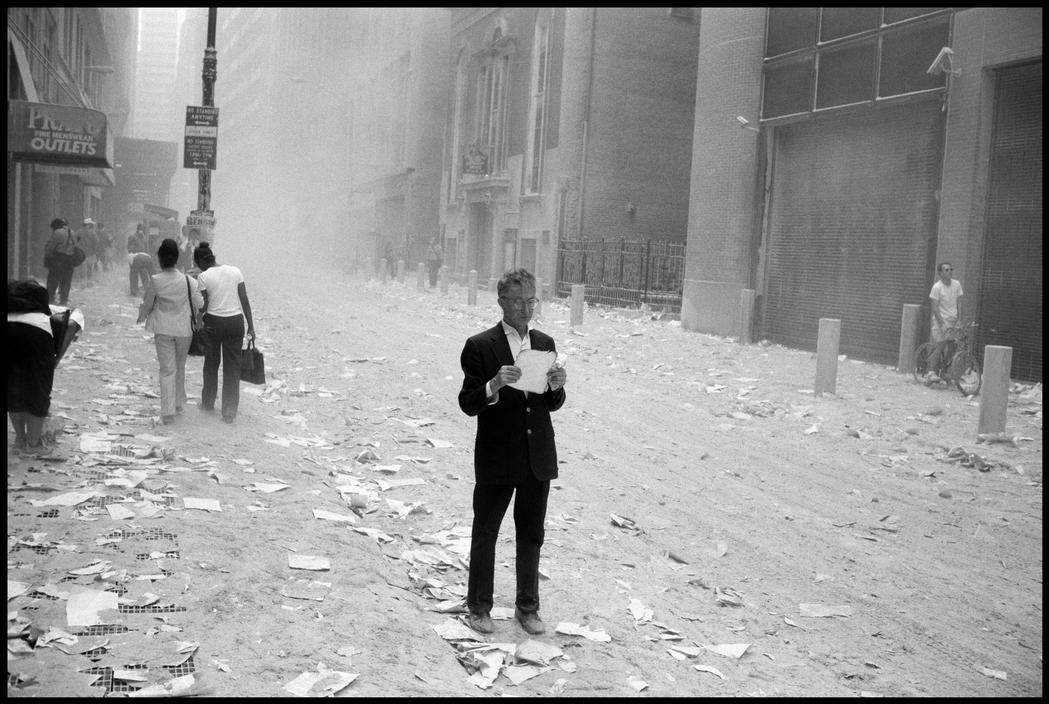 USA. NYC. 9/11/2001. A dazed man picks up a paper that was blown out of the towers after the attack of the World Trade Center, and begins to read it. – photo by Larry Towell
