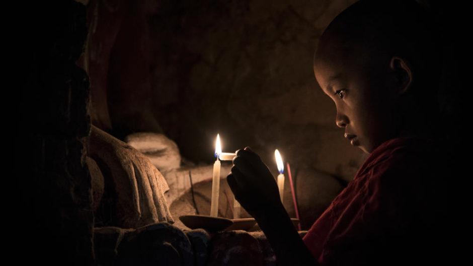 © Pierre Chancy - Un jeune moine allumant des bougies dans un temple de Bagan, Myanmar