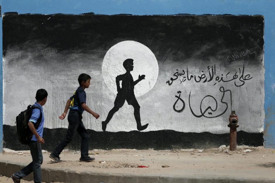 © Thomas Coex - AFP PHOTO - Photo éditée par Marina Passos - Elle représente deux écoliers palestiniens marchant le long d'un mur de l'école des Nations Unies de Beit Hanun, recouvert de graffitis, dans le Nord de la bande de Gaza le 9 mai 2016.