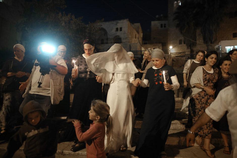 """© / Menahem Kahana - AFP PHOTO - Photo éditée par Marina Passos - Cette photo représente une jeune mariée israélienne, Yael Levi, accompagnée de ses amis et ses proches vers la place près de la """"Cave des Patriarches"""", aussi connue sous le nom de la Mosquée Ibrahimi et lieu saint des deux communautés juives et musulmanes, lors de son mariage (22 septembre 2016)."""