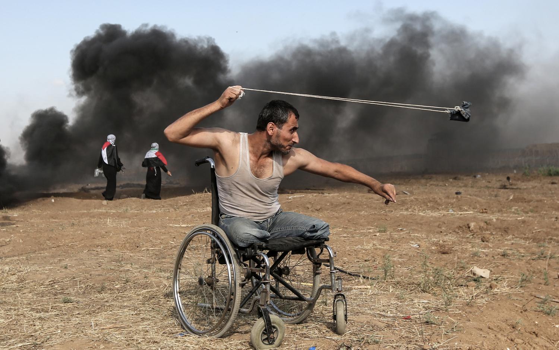 Le Palestinien Saber al-Ashkar, 29 ans, lance des pierres durant des affrontements contre les forces israéliennes, le long de la frontière de la bande de Gaza à l'Est de la ville de Gaza, le 11 mars 2018. Les Palestiniens manifestent pour le droit au retour dans leur terre d'origine, désormais considérée comme territoire israélien © AFP PHOTO / MAHMUD HAMS