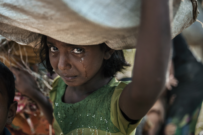 Une Rohingya pleure, traumatisée après des jours de marche, avec peu de sommeil, alors que des milliers de personnes fuyant le Myanmar sont coincées sous un soleil brûlant sur une rizière boueuse attendant d'être admise dans les camps par les gardesfrontières du Bangladesh à Anjuman Para, Cox's. Bazar, Bangladesh le 16 octobre 2017 © Paula BRONSTEIN
