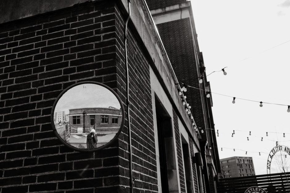 Une personne qui fait un autoportrait dans un miroir à l'extérieur.