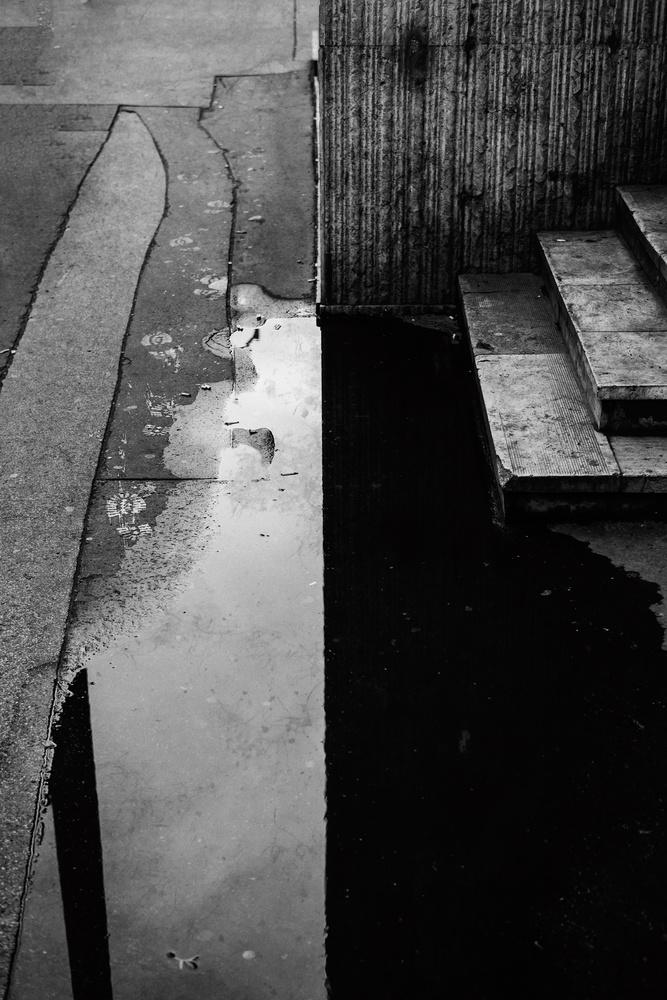 Une flaque d'eau avec le reflet d'un mur.